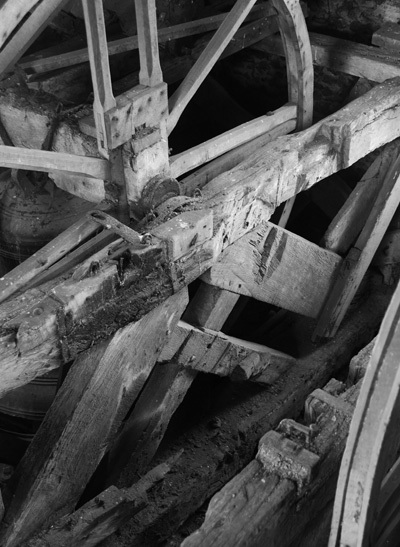 The Whitechapel bell is visible in the background with the bell pit for one of the stolen bells in the foreground showing the rotated timbers and multiple bearing mounts.